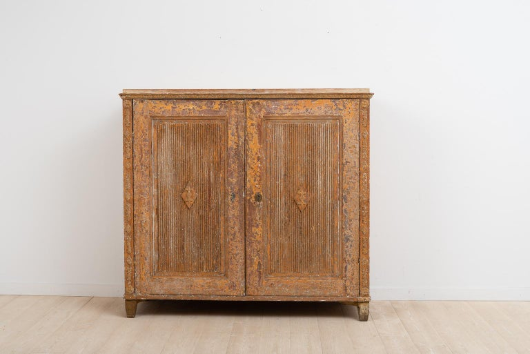 Gustavian sideboard from northern Sweden. Rustic patina. The sideboard has an unusual construction with drawers on the inside. Gustavian decor in the form of pastellage on the doors and sides. There is some smaller damages to the decor on the top's