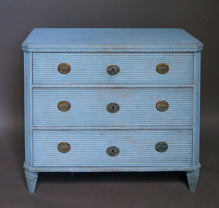 Chest of drawers in the Gustavian style, Sweden, circa 1880, with three reeded drawers. Dentil molding under the shaped top, reeded corner posts and tapering square feet. Period brass pulls and escutcheons.