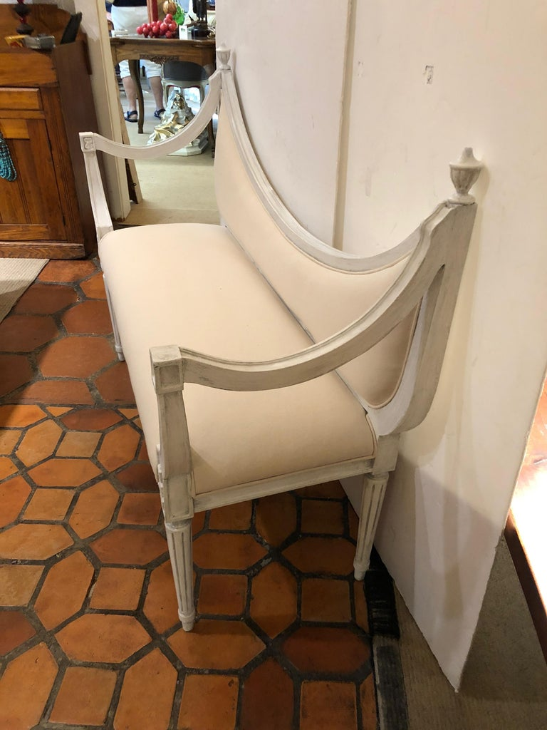 Dreamy scoop back settee bench with grayish white painted wood, reeded legs and wonderfully shaped arms, urn shaped finials, newly upholstered in white duck.  Measures: Seat height 17.