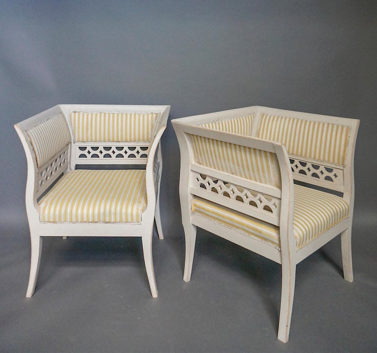 Pair of large armchairs in the Gustavian style, Sweden circa 1910. The high arms and backs are upholstered above pierced panels, and the flaring arms continue into saber legs in an elegant curve. The deep upholstered seats provide a comfortable nook