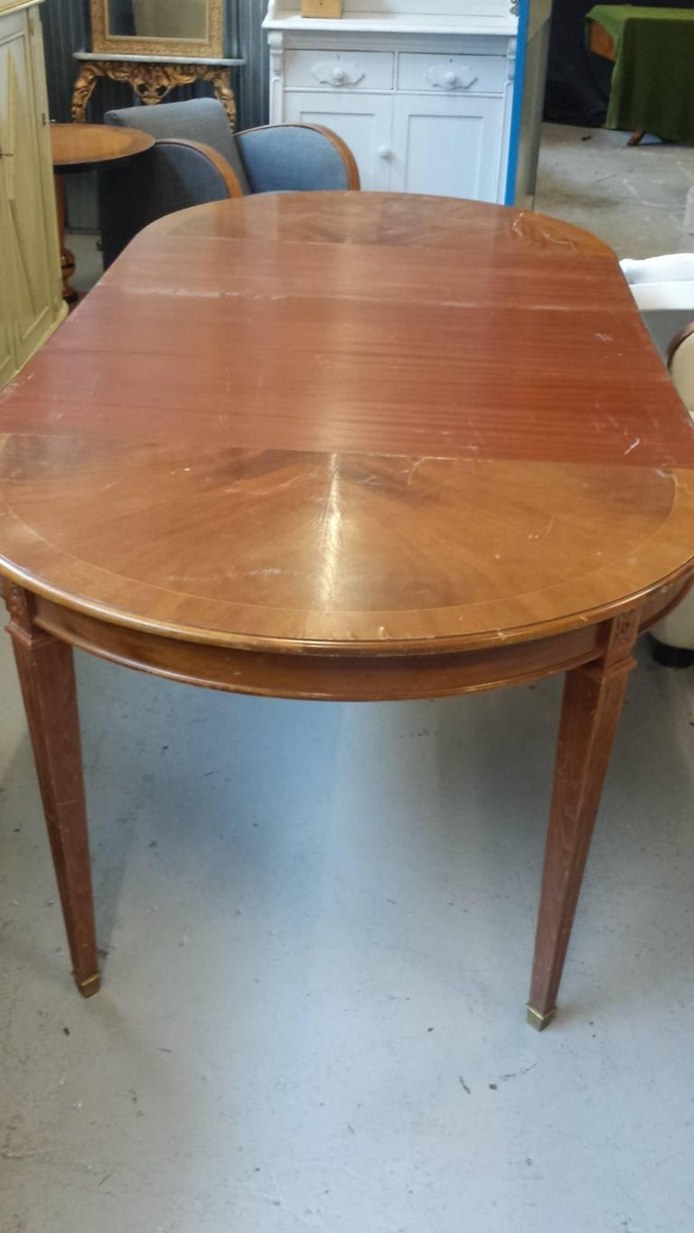 Unusual early 1900s Gustavian extendable dining table with top grade quilted mahogany veneers,  Lovely pyramid fluted legs with a rosette detailing and brass feet.  It is approximate 110 cm in diameter un-extended and goes to 230 cm extended