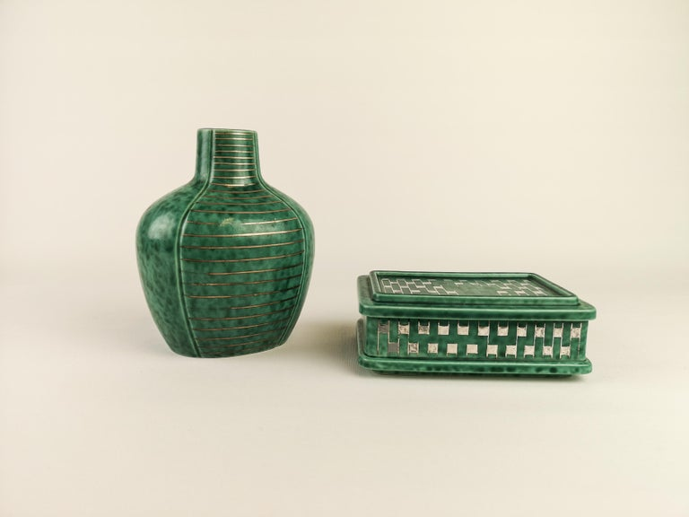 Wondeful pieces from Gustavsberg and the modell name Argenta, design Wilhelm Kåge during the 1930s. One vase with silver lines and one box with silver decorations.   Box H: 5,5 cm W:10 cm L:14,5 cm Vase H: 15,5 cm W:12,5 cm.