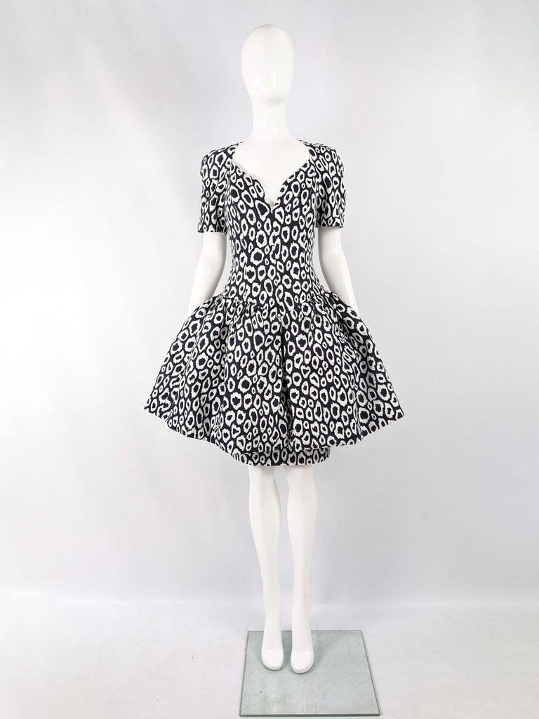 An incredible vintage womens evening / formal party dress from the 80s by luxury French fashion designer, Guy Laroche. In a darkest bluish-grey and white patterned fabric with a layered skirt, the top flared skirt is structured with a horsehair