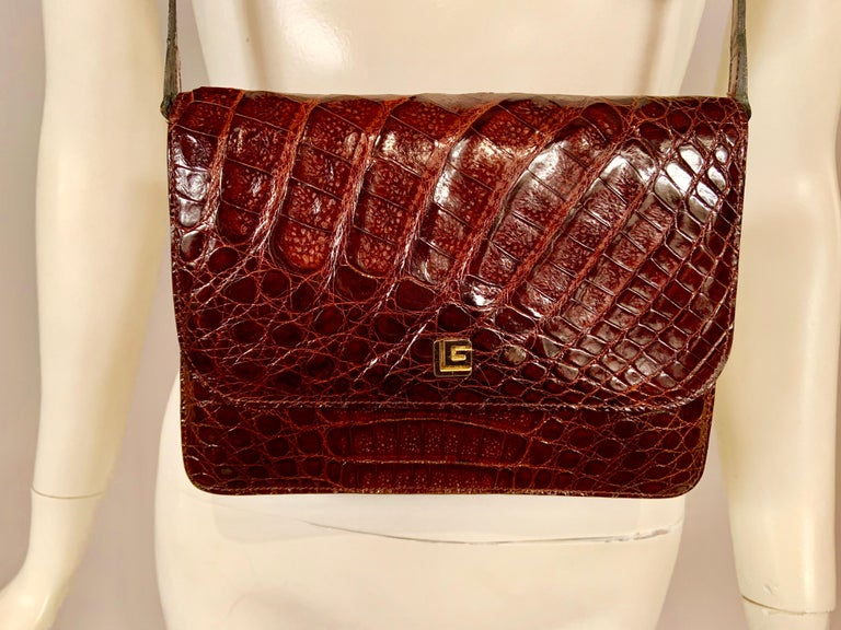A sleek brown alligator shoulder bag or cross body bag with a slip pocket on the outside,  and a logo snap closure is a chic smaller size. It is lined in brown leather with a divided interior. The back section has a zippered pocket and a slip pocket