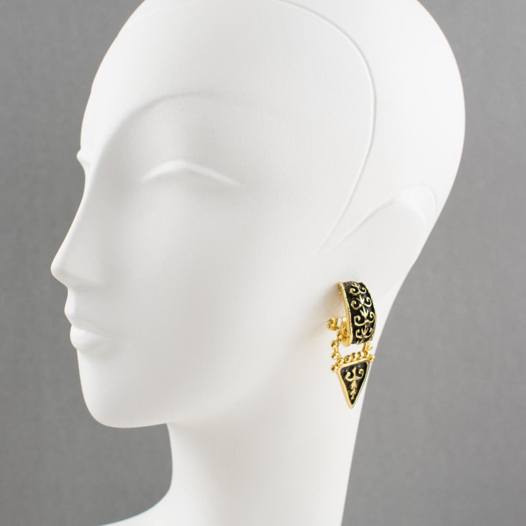 Elegant Guy Laroche Paris signed clip-on earrings. Dangling shape with Renaissance-inspired design, gilt metal all carved and textured ornate with black enamel. Engraved signature at the back: 'Guy Laroche - Paris'.  Measurements: 2.13 in. long (5.3
