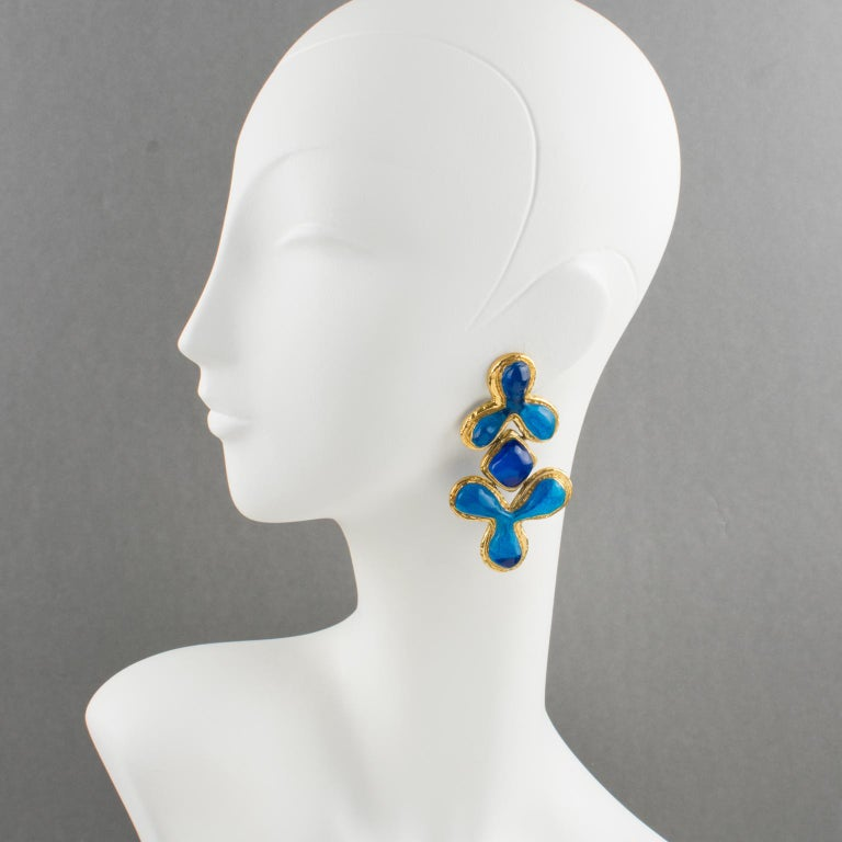 Elegant Guy Laroche Paris clip-on earrings. Dangling shape with carved and textured gilt metal framing, ornate with cobalt blue resin carved cabochons. Engraved signature at the back: