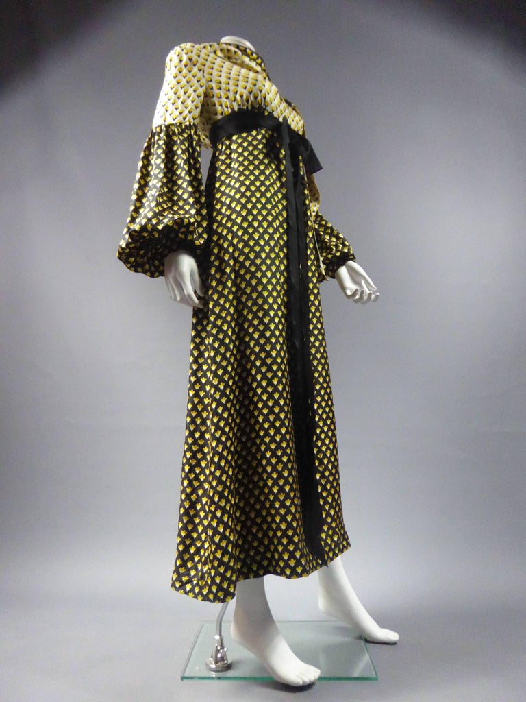 Circa 1970 France  Long printed silk dress by Guy Laroche. Printed with reverse effect of negative / positive. Empire waist dress highlighted by a belt under the chest in a black satin ribbon bow. Long dress with flared skirt, black fabric strewn