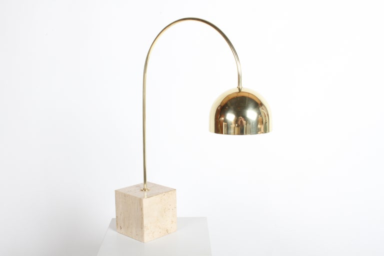 Beautiful Harvey Guzzini brass arc table lamp on travertine base. Brass arm and shade have been polished to a warm butler finish and lacquered. Inside the shade has new white paint. Has been rewired with new clear cord that has inline on/off switch.