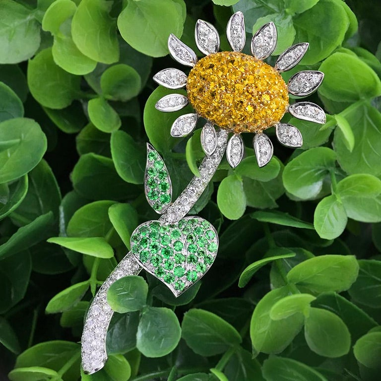 Designed by the master craftsman of g. Verdi of Italy. This sunflower brooch is very special, with 14 petals and stem pave set with round brilliant diamonds. The center pistil is set with round brilliant yellow sapphires and the leaves are set with