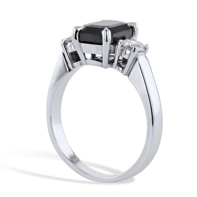 This handmade black and white diamond engagement ring conjures the thought of the night sky punctuated by starlight. A  2.34 carat emerald cut black diamond is four-prong set at center and feature 0.40 carat of accent diamonds (H/I/I1) on both sides