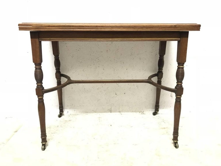 H W Batley, attributed Collinson & Lock. A fine quality Anglo-Japanese rosewood fold over card table opening to reveal the original gold baize with embossed sunflower details to the corners. The slightly splayed, turned and incised legs united by a