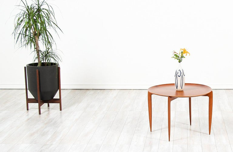 Versatile Danish Modern tray table designed by H. Engholm & Svend Åge Willumsen for Fritz Hansen in Denmark, circa 1950s. This extraordinary and practical table design features a sculpted teak wood base with a spider leg base and a rounded teak tray