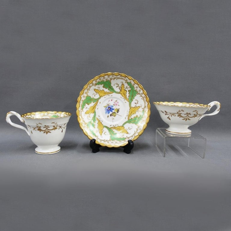 An H & R Daniel English porcelain teaset comprising ten cups, six saucers, milk jug, sucrier, slop bowl and cake plate. The set is made up of 4 true trios which is a coffe cup,a tea cup and a saucer. 2 additional tea cups and saucers make up the