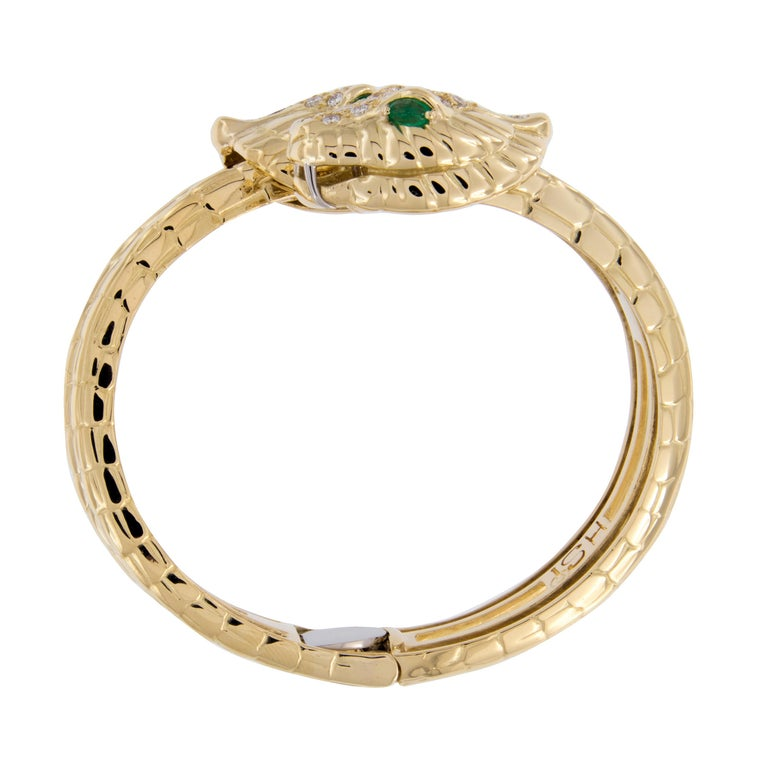 Stunning double serpent bangle bracelet with hinge for ease of wearing by H. Steppenjay of New York. 3.33 Cttw of pave' set diamonds adorn the serpents heads and vivid emeralds comprise his piercing eyes. Bracelet can also function as a tennis
