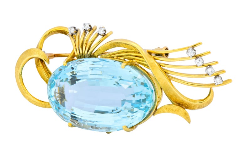 Centering a prong set oval cut aquamarine weighing approximately 55.00 carats, transparent and a vibrant sky blue color  Scrolled and linear gold elements accented by diamonds weighing approximately 0.15 carat total, E/F color and VS