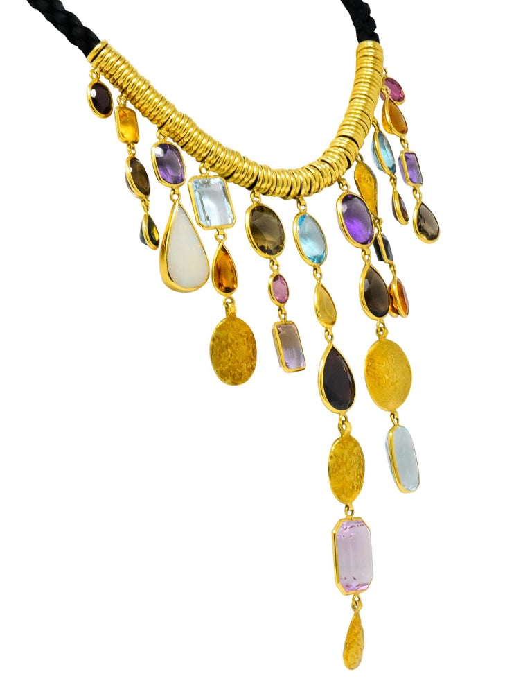 Designed as a woven cord necklace set to the front with gold roundels and eleven graduated drops  Drops are bezel set with various colored and shaped gemstones with textured gold accents  Featuring opal, garnet, citrine, amethyst, ametrine, smokey