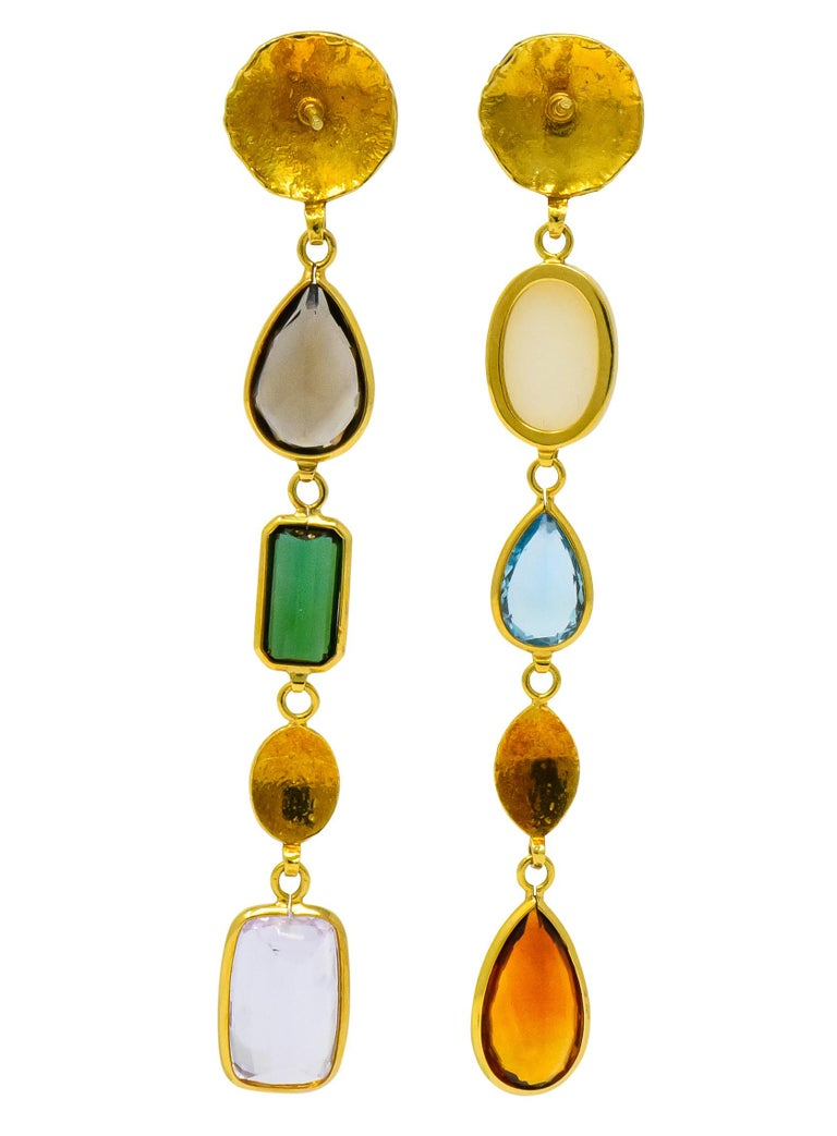 Each with textured gold disc surmounts, connected to bezel set drops comprised of various shaped and colored gemstones  One with oval cabochon opal, pear cut blue topaz, and pear cut citrine   The other with pear cut smokey topaz, rectangular cut