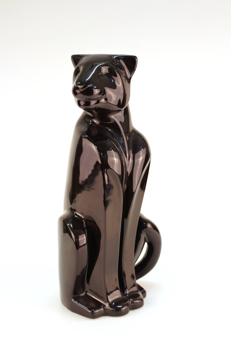 A ceramic sculpture of a seated black panther, made by Haeger in the 1980s in the United States. The piece is made in an Art Deco style and includes the original label on the bottom. In very good vintage condition.