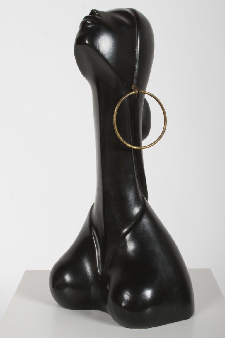Stylized African female with elongated neck, ebonized carved wood with large brass earring, in the style of Hagenauer - Austria. In nice vintage condition, some scuffs. Unsigned. Measures: 16