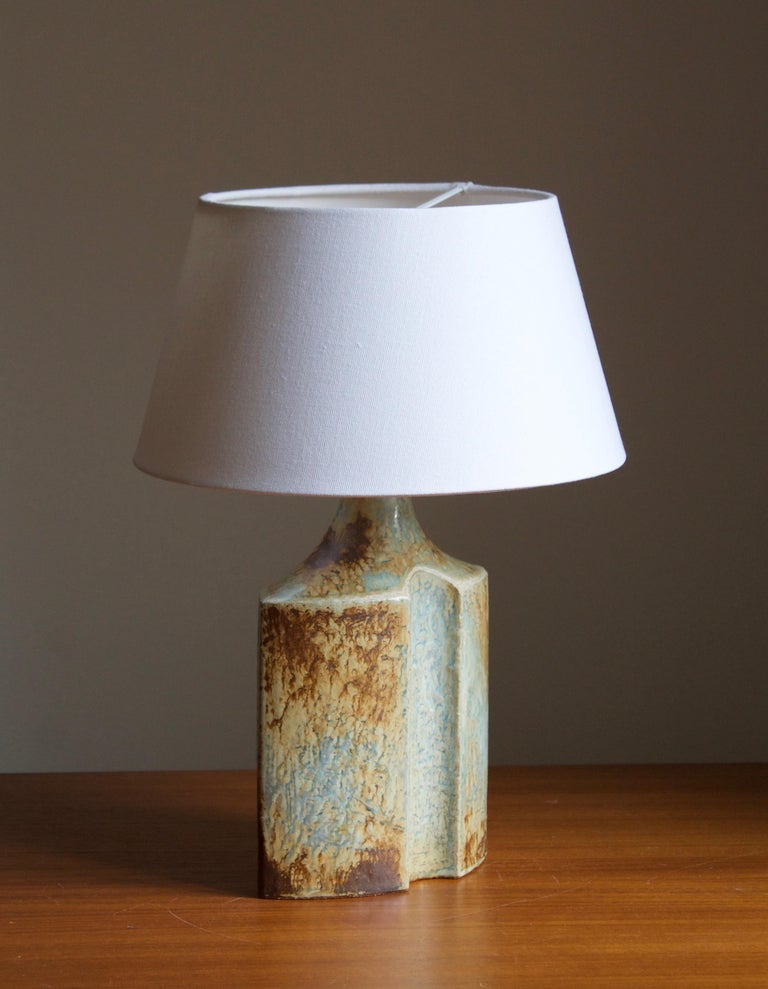 A table lamp produced by Søholm Keramik, located on the island of Bornholm in Denmark. Features a highly artistic glazed decor.   Sold without lampshade. Stated dimensions exclude the lampshade. Height includes socket.  Other designers of the