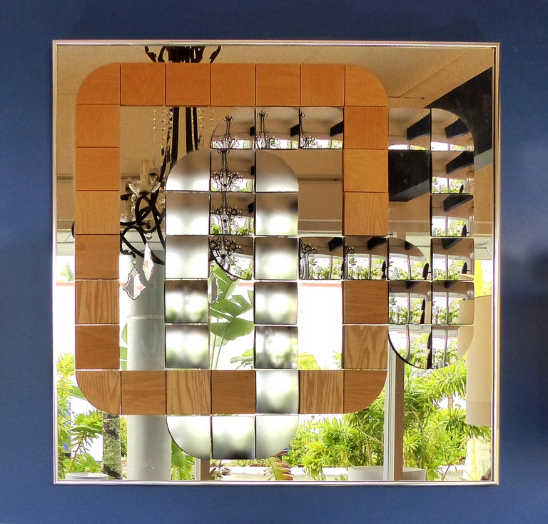 Offered for sale is a Hal Bienenfeld geometric optical art wood and mirror decorative wall composition. The mirror incorporates curves and movement with the use of different finished and shaped mirrored panels contrasting with wood panels. The