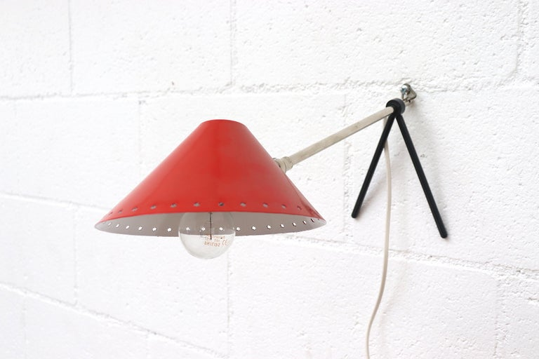 Hala Zeist red enameled metal table or wall lamp with pinocchio shade. Versatile small lamps that function as both table lamp and wall lamp. Great as bedside lamps. Priced individually. In original condition with wear consistent with age and use.