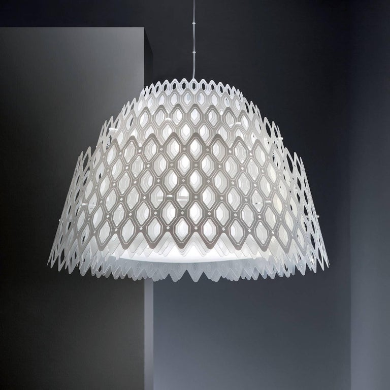 Part of the Charlotte collection designed by Doriana and Massimiliano Fuksas, the silhouette of this stunning ceiling lamp evokes the movement of waves, in its multiplying of layers that open up to form its shade, adorned with a honeycomb-inspired