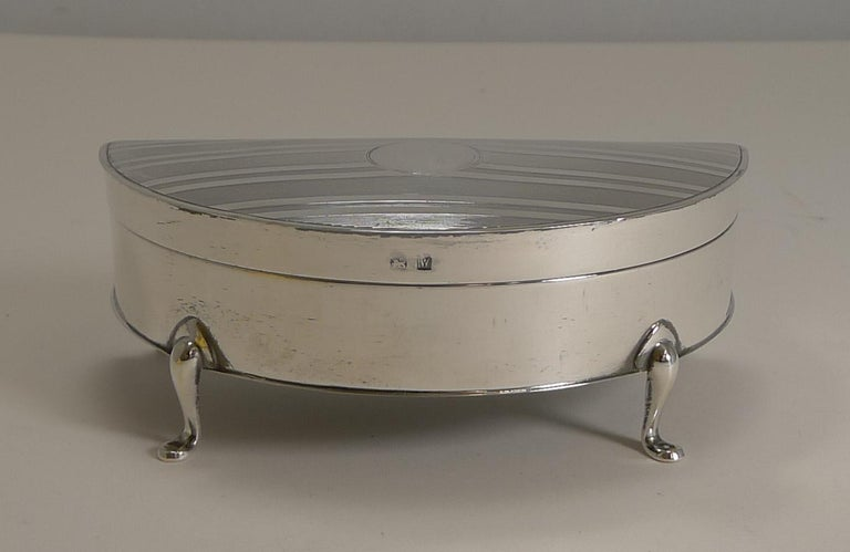 A wonderful demilune or half-moon shaped jewellery box made from sterling silver standing on four elegant cabriole legs.  The top of the lid is engraved with a smart linear engine turned decoration with a central circular vacant cartouche.  The