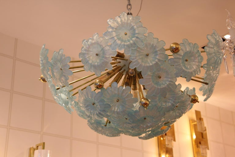 This very unusual half Sputnik chandelier features a multitude of brass rods, some ending with brass balls and others ending with large blue flowers in Murano glass. All the rods have got different length so that flowers are on different levels and