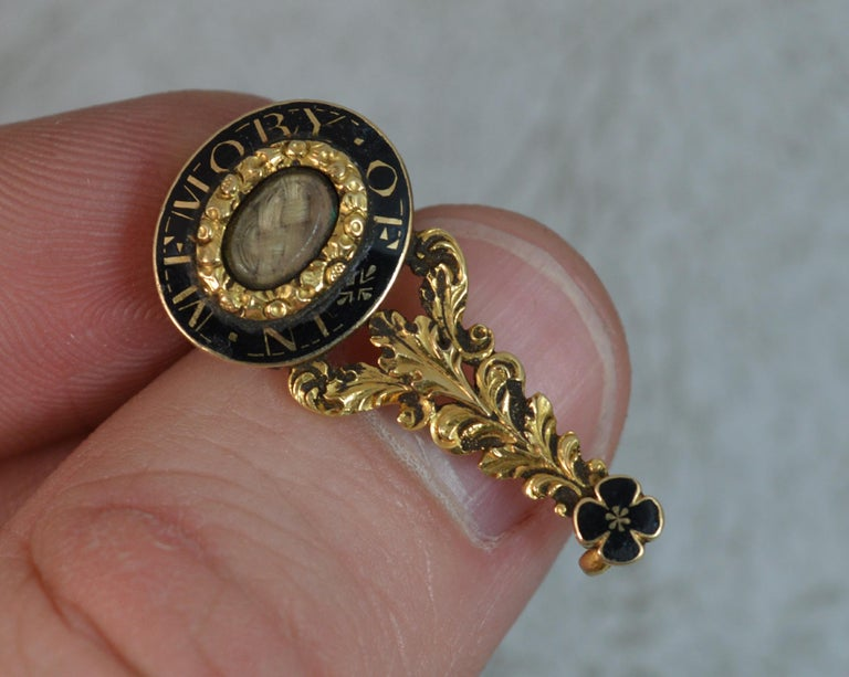 A stunning Georgian period brooch c1800. Halley's comet example. Solid 15 carat gold. Unusually designed also as a piece of mourning jewellery. One end set with an oval braided hair locket section to the centre of an enamelling In Memory Of border.