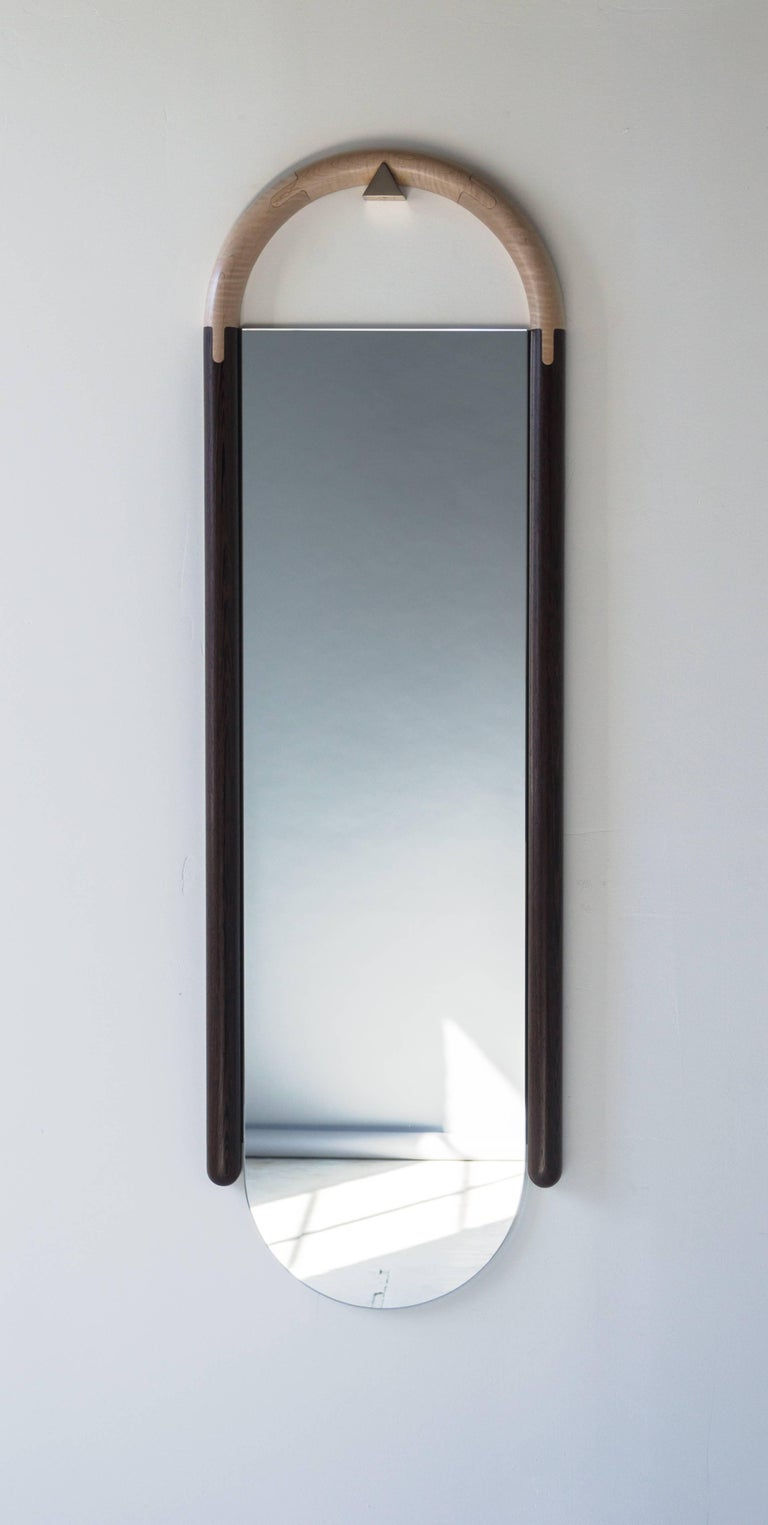 The wall mounted Halo Mirror mirror hangs and self-levels on a triangular bronze peg. We use a primitive but efficient sand molding process to cast the peg. The surface is left a bit rough even after polishing to reflect our process. Installation