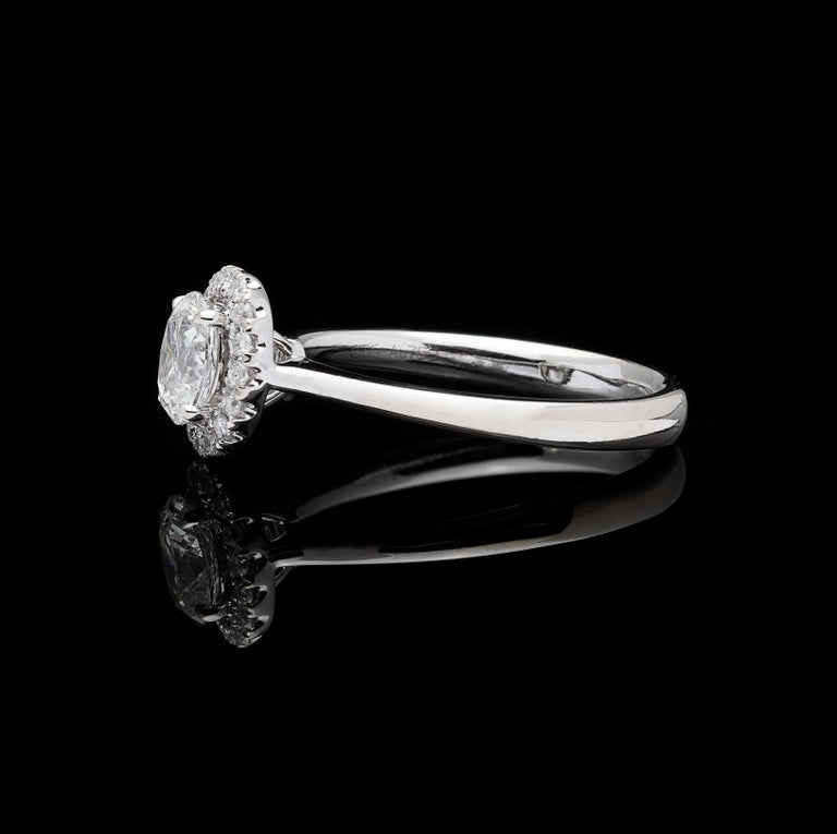 Delicate and feminine, this 18k white gold engagement ring centers a 0.55-carat oval-cut diamond, set within a halo of 16 round brilliant-cut diamonds, for a total diamond weight of approximately 0.71 carats. The ring weighs 2.9 grams, and is