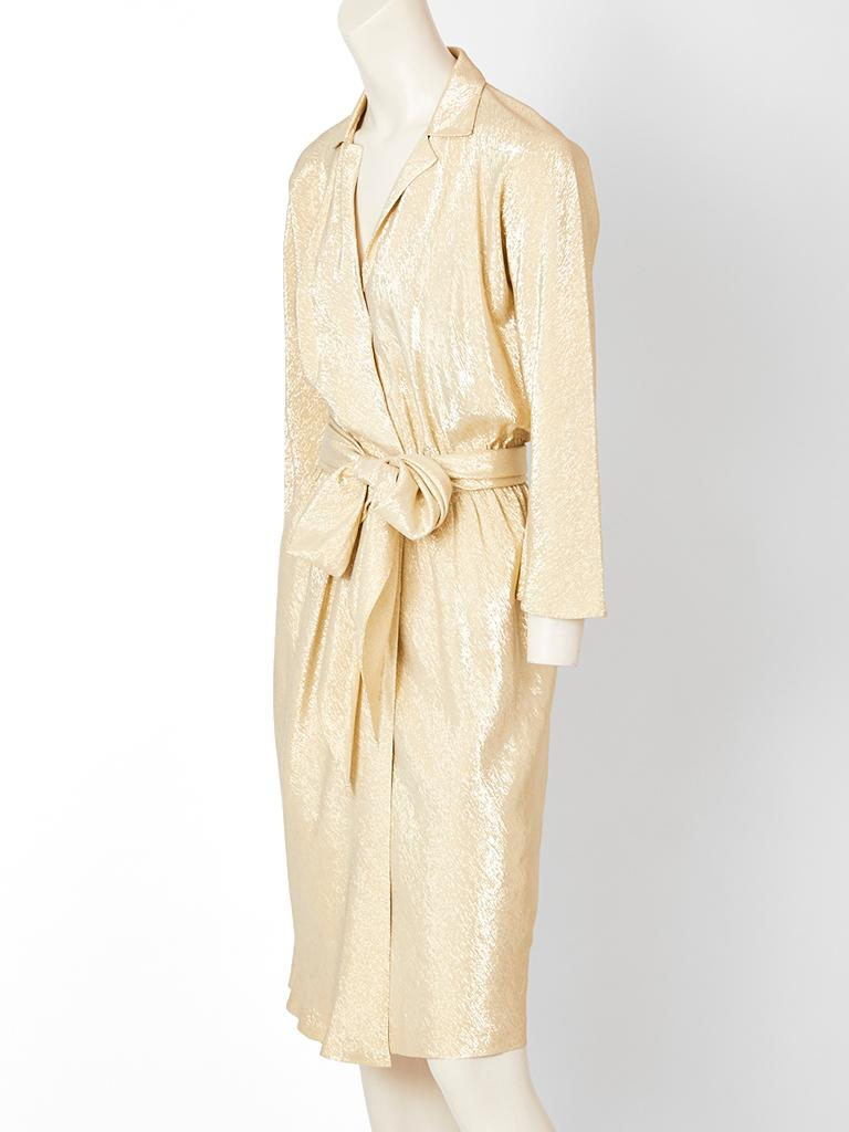 Halston, gold lame, bias cut, wrap dress, having a deep V, with small collar, long sleeves and a self belt/ sash that can be tied at the waist to be made into a generous bow. C. 1970's.
