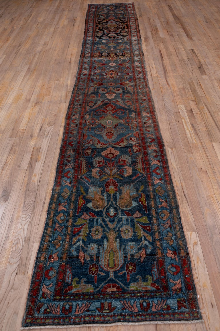 This rather flat west Persian runner displays an abrashed green to deep blue-green field with a giant flower and leaf pattern in dark brown, light blue, rust and golden-brown. The medium blue border displays a very simple palmette and diagonal leaf