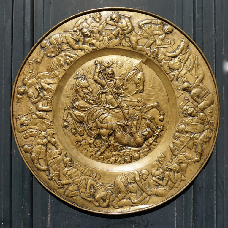 A 19th century hammered brass dish of unusual size in the historical style representing a battle scene between Romans and Barbarians, in the middle fighting generals on horseback, the frieze surrounding them showing infantry engaged in battle and