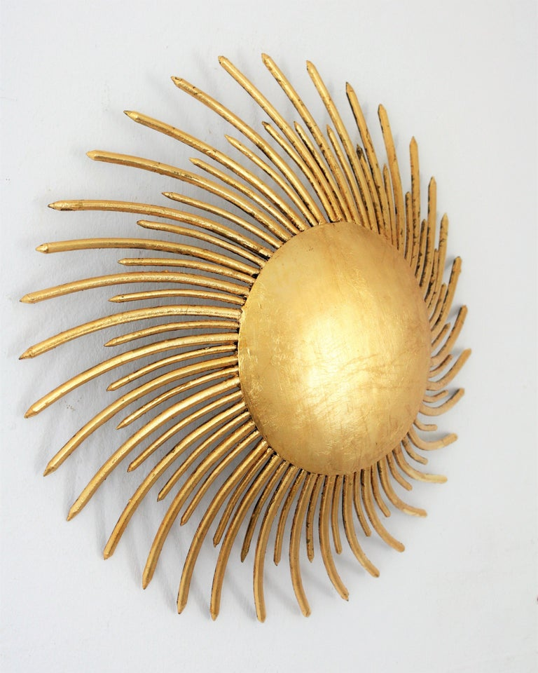 Unusual hand-hammered gilt iron sunburst ceiling light fixture or wall sconce with gold leaf finish and Art Deco accents in transition to Brutalist style. A highly decorative piece with iron nails in two sizes as sun beams surrounding the central