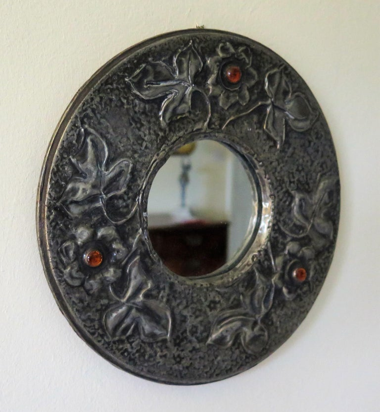 This is a very decorative, English, wall mirror of small diameter, made of hammered Pewter, with amber glass cabochons and dating to the English Arts and Crafts period, circa 1900  The mirror is circular with a central mirror glass with a small