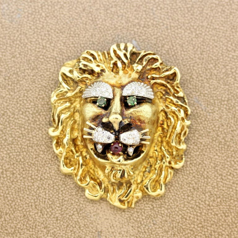 A classic whimsical brooch by Hammerman. The brooch is hand sculpted in 18k yellow gold in the form of a mighty yet sweet lion. It has emerald eyes along with a cabochon ruby mouth and diamond eyebrows and whiskers. The lion's mane is beautifully