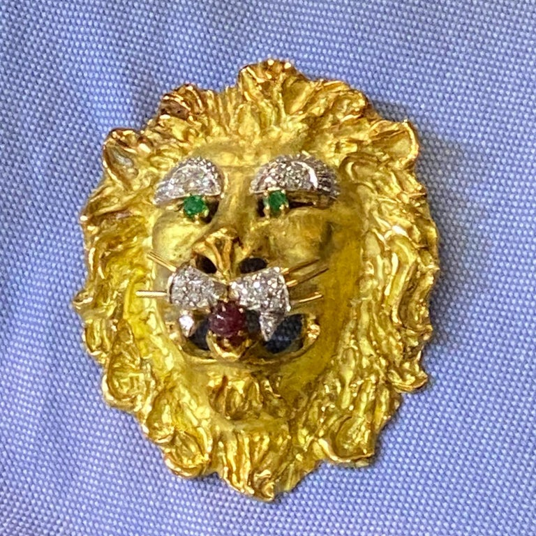Vintage Lion's Head Pendant/Piin, by Hammerman Brothers, is fashioned in 18 karat yellow gold. The piece can be worn as a pendant or pin, and features diamonds, emerald eyes, and ruby mouth. The 23 round brilliant cut diamonds weigh approximatel .50