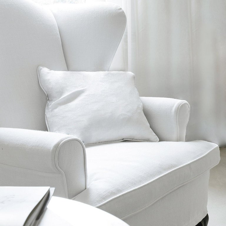 This luminous armchair, raised on softly curved feet, strikes with its voluptuous volumes covered in white fabric (removable) and accented with tone-on-tone piping. A superb solution for rustic-chic decors, it features a sturdy wooden structure