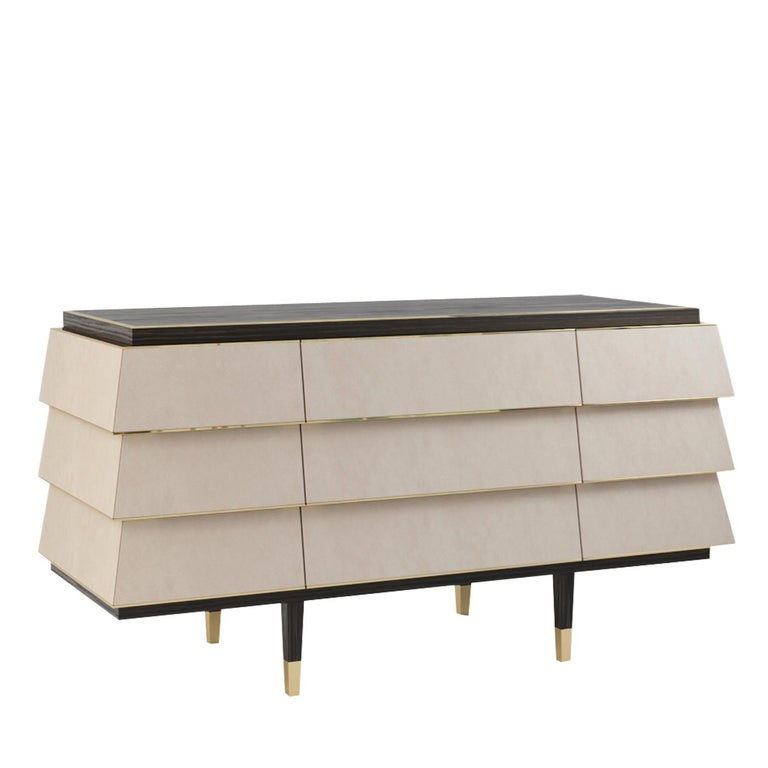 Distinguished by a stunning geometrical design and sharp lines, this exquisite dresser will be a statement piece in a refined contemporary interior. It consists of nine white-lacquered, wide drawers and a rectangular dark brown wooden top, graced by