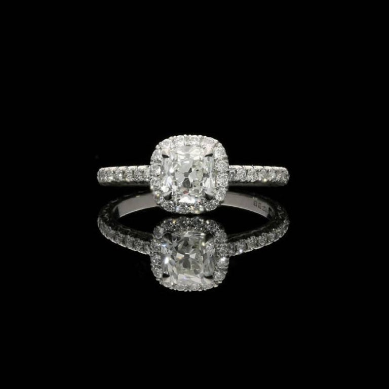A charming old cut diamond and platinum cluster ring by Hancocks, centred on a beautiful cushion shaped old mine cut diamond weighing 0.90 carats and of J colour and VS1 clarity, claw set within a diamond halo surround between fine diamond-set