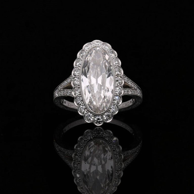 A stunning oval cluster diamond ring by Hancocks centred with a beautiful antique-cut moval shaped diamond weighing 3.35 carat and of H colour and VS2 clarity within a fine millegrained rub-over setting surrounded by a halo of single cut diamonds in
