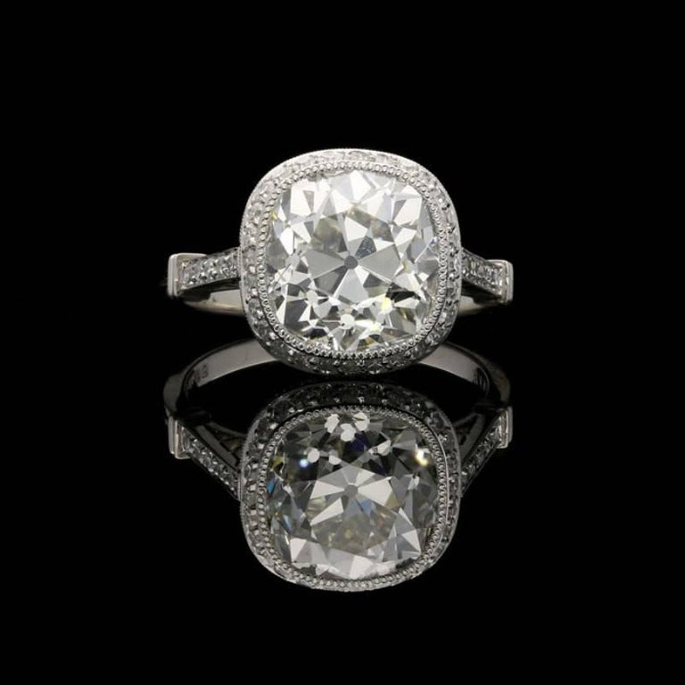 A stunning cushion shaped diamond and platinum ring by Hancocks, centred on a beautiful old mine brilliant cut diamond weighing 4.51 Carats and of J colour and VS1 clarity set within a rubover millegrain surround to a finely crafted handmade