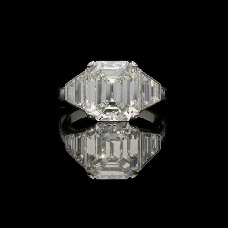5.01 carat E VS2 vintage emerald cut diamond with GIA certificate 4 x trapezoid diamonds weighing a combined total of 1.09 carats UK finger size L, US size 6, can be adjusted to your own finger size 7.4 grams  A stunning diamond and platinum ring by