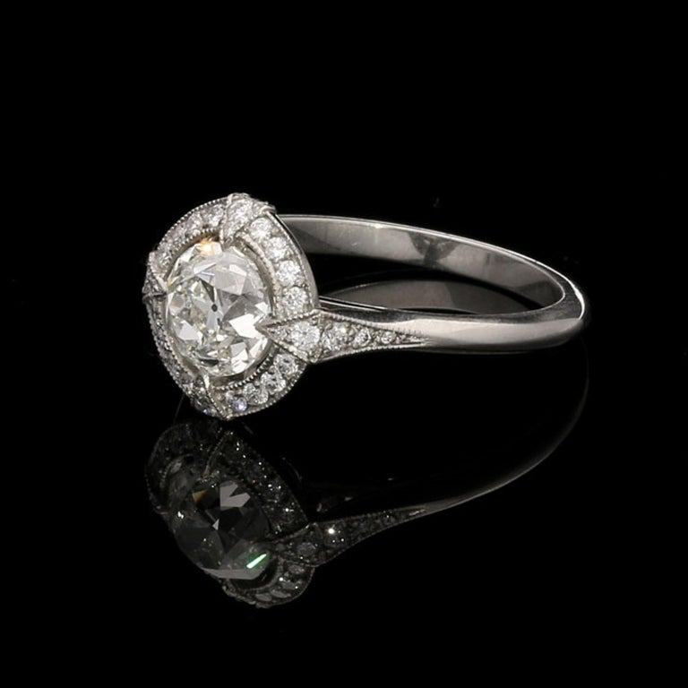 1.15ct I VVS1 Old European Brilliant Cut Diamond Cluster Ring by Hancocks.  The diamond is set in a floating effect by four diamond set folds emanating from a diamond set surround and continuing to the gallery and shoulders of the ring.  1.15ct I