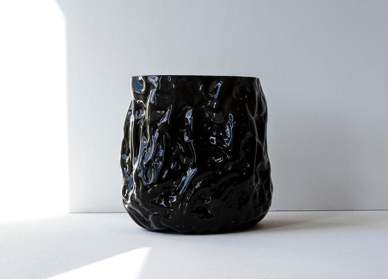 Unique Piece. Hand blown glass vase made in forms of soft clay that are shaped by hand just before blowing the glass into the form. The process makes all pieces unique and gives them a wrinkled surface. NOTE, small parts of clay from the production