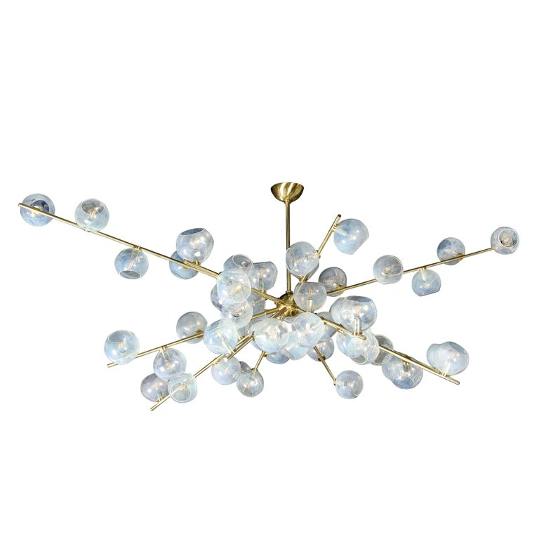 This stunning and monumental modernist chandelier is hand blown and handcrafted. It features an abundance of organic hand blown iridescent shades- each uniquely formed- attached to brass arms that appear to