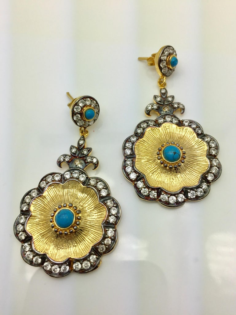 Two-tones: silver and gold, coexist in harmony, enhanced by dozens of twinkling CZ stones in flower shaped turquoise and CZ drop earrings. These earrings hit all the trends in an elegantly beautiful way. Earrings have a post closure for pierced