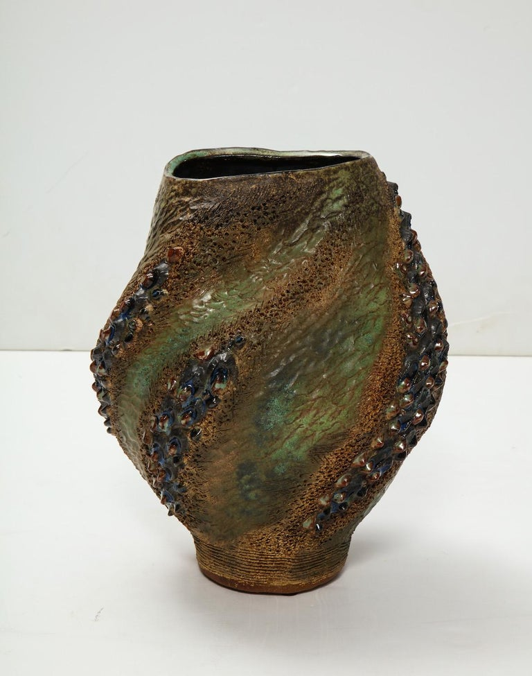 Hand-built earthenware vase with texture and movement throughout. Great earth tone glazes suggesting flames. Artist-signed and dated on underside.
